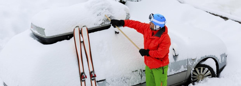Man haaldt sneeuw van zijn auto