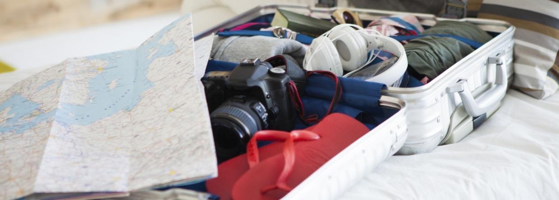 Koffer met bagage op bed