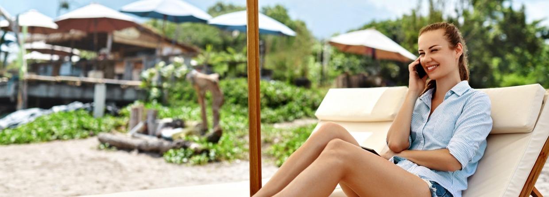 Vrouw met mobiel op een strandstoel