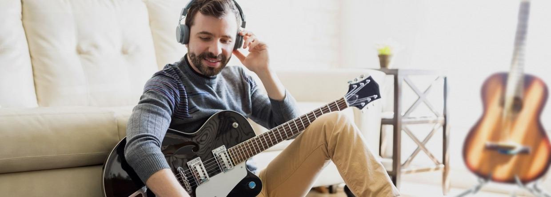Man speelt thuis gitaar