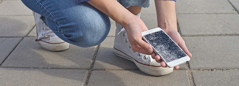 Persoon die een kapotte smartphone vasthoudt met een gebarsten scherm