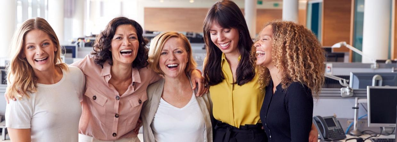 Lachende vrouwelijke collega's die samenwerken in een modern kantoor