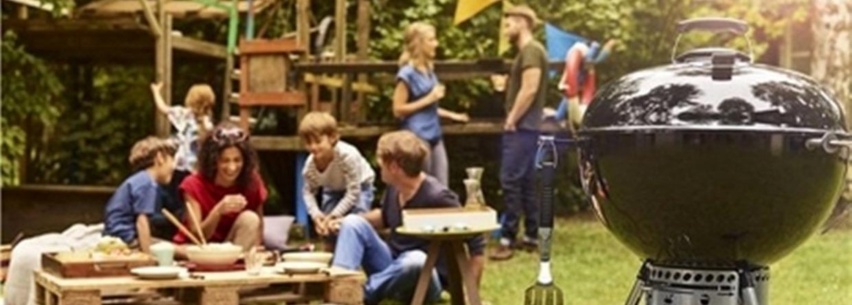 Vrienden lekker aan het barbecuen in de tuin