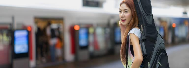 Jonge vrouw met gitaar op het station
